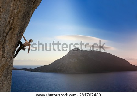 Silhouette of man climbing on rock mountain at sunset - stock photo