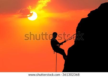 Silhouette of man climbing on rock (mountain) at sunset - stock photo