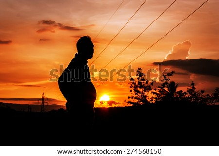 silhouette of man fat standing at sunrise in the mountains and high voltage electricity pylon - stock photo