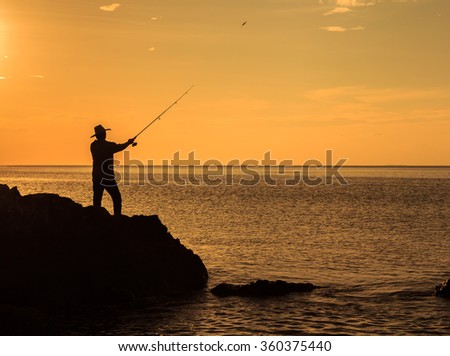 Silhouette of man fishing in the evening.