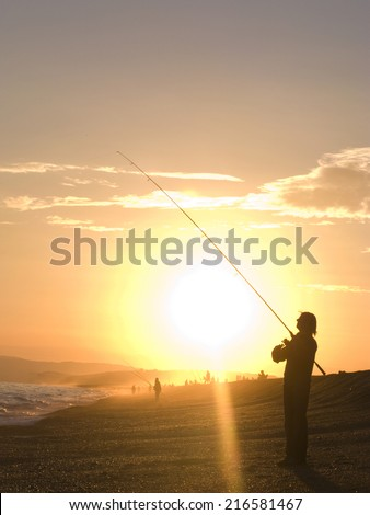Silhouette of man fishing with fishing rod at ocean at sunset