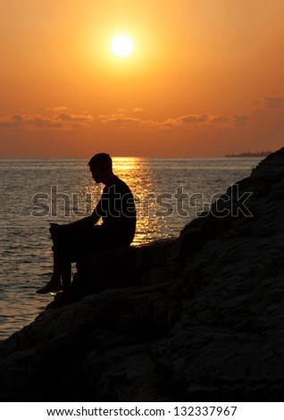 Silhouette of man from side sitting on a rock and enjoying the sunset