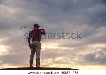 silhouette of man golfer with golf club at sunset. back view - stock photo