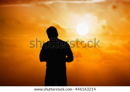 Silhouette of man hearing music on the beach at sunset.
