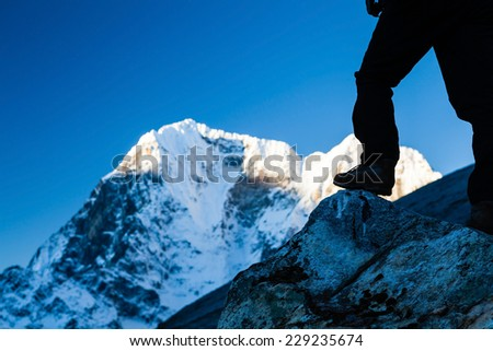 Silhouette of man hiking in Himalaya Mountains in Nepal. Climbing in high mountains wilderness sunrise landscape. - stock photo