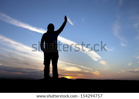 silhouette of man holding up his hand
