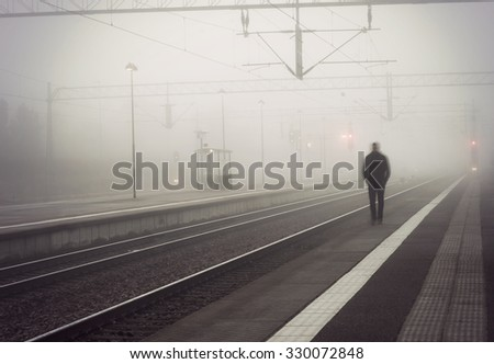 silhouette of man in blurred motion walking on platform, waiting for train on foggy day