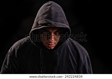 Silhouette of man in the hood or hooligan over dark background - stock photo