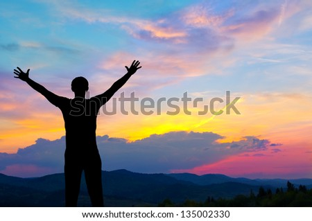 Silhouette of man in the mountains at colorful sunset