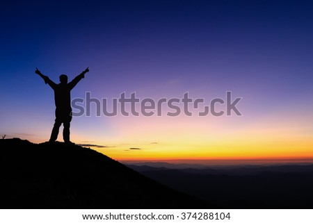 Silhouette of man is standing and spread hand on top of mountain to enjoy colourful sunset sky.