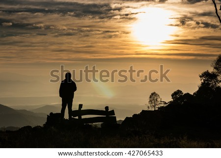 Silhouette of man is standing on top of mountain at sunrise.