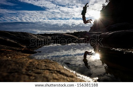 silhouette of man jumping in norwegian landscape - stock photo