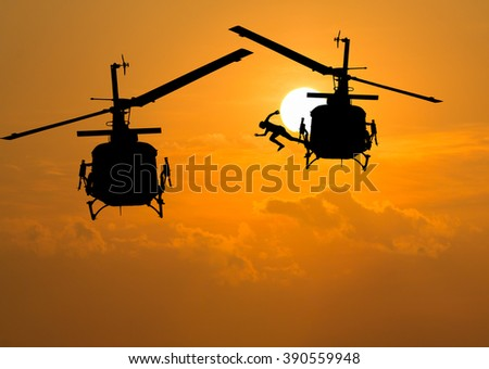 silhouette of man jumping out of a helicopter