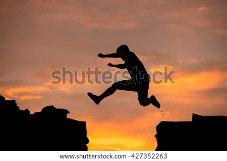 Silhouette of man jumping over cliff on sunset background , business concept