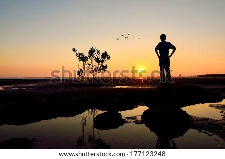 Silhouette of Man looking to the sun near the beach when the sun goes down - stock photo