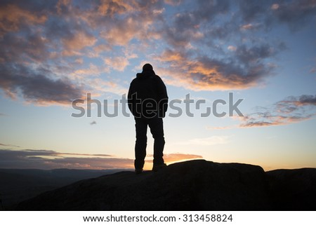 silhouette of man looking towards the sunset - stock photo