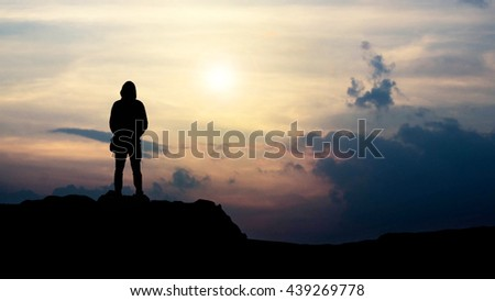 silhouette of man looking towards the sunset
