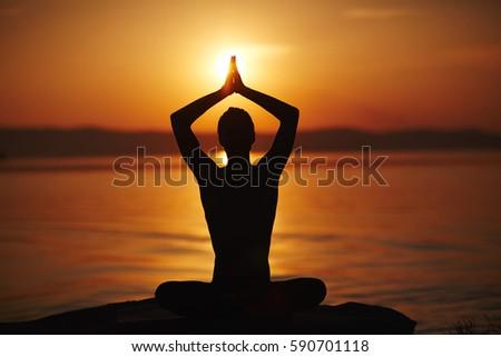 silhouette man meditating lotus pose his stock photo