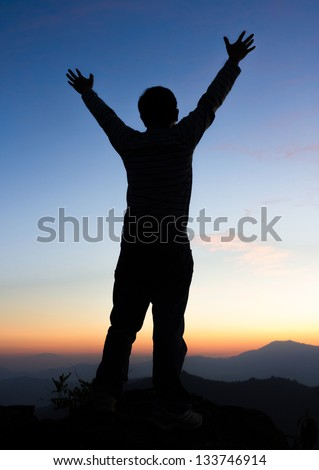 Silhouette of man on a summit with upraised arms  on the top mountain with the sunset, Praise for GOD. - stock photo