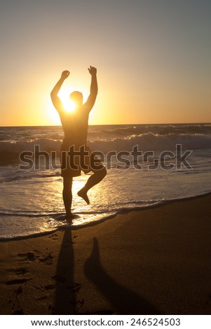 Silhouette of man on sunset with hand up