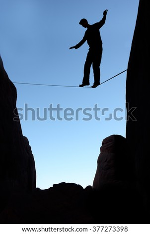 Silhouette of man on the rope concept of risk taking vertical image