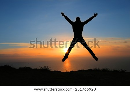 silhouette of man on the sunset on rock - stock photo