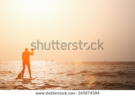 Silhouette Of Man Paddleboarding At Sunset - stock photo
