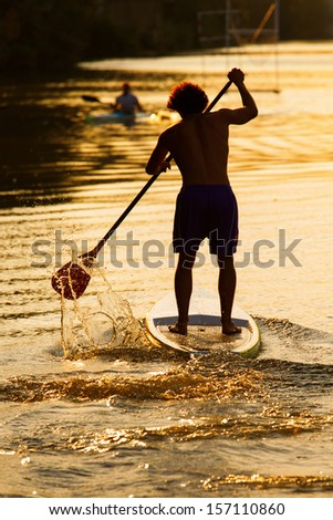 Silhouette of man paddleboarding at sunset, Florence river, Italy, recreation sport paddling ocean beach surf - stock photo