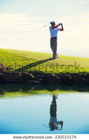 Silhouette of Man Playing Golf on Beautiful Course, Reflection in Water - stock photo