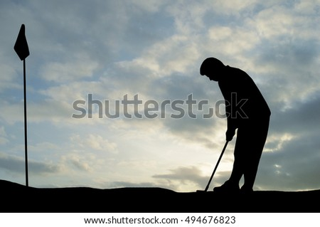 Silhouette of man playing golf, sun, beautiful colorful sky and clouds behind. Golfer approach to shot ball into the hole with iron on green.