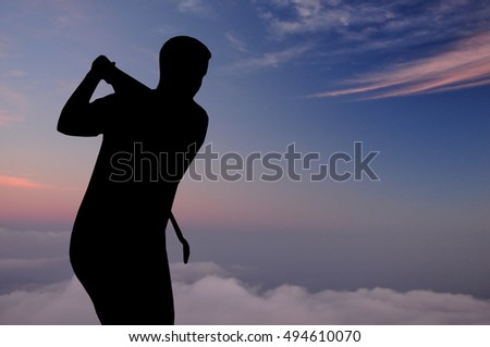 Silhouette of man playing golf, sun, beautiful colorful sky and clouds behind. Golfer hitting golf ball down the fairway  with club on course.