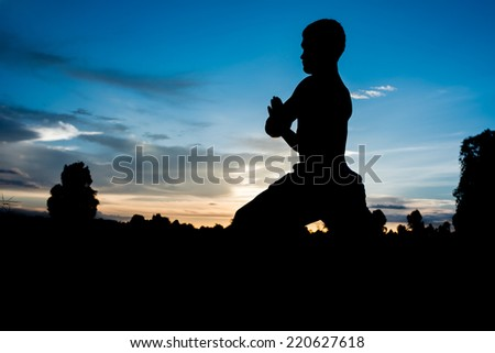 Silhouette of man practicing yoga with beautiful sunset