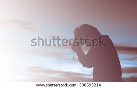 Silhouette of man praying  - stock photo