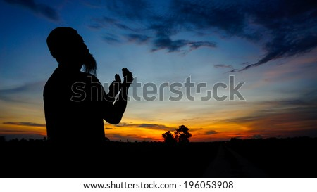 Silhouette of man praying during sunset