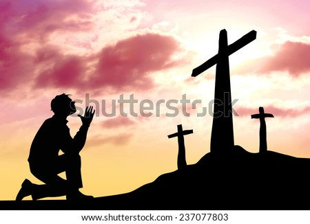 Silhouette of man praying to a cross with heavenly cloudscape sunset concept for religion