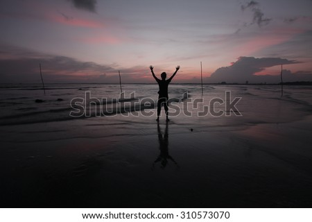 Silhouette of Man Raising His Hands or Open arms when sun rising up - stock photo