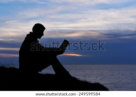 Silhouette of man reading in the sunset light, sea, ocean, nature - stock photo