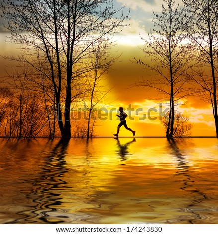 Silhouette of man running at sunset - stock photo