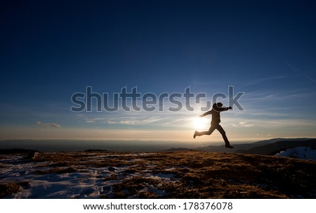 silhouette of man running in sunset sky  - stock photo