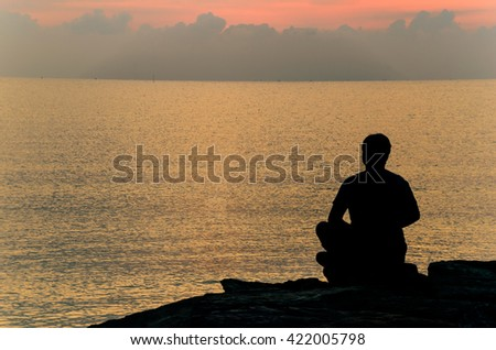 Silhouette of man sitting meditation  by the sea in the morning.