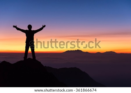 silhouette of man standing and spread hand on the top of mountain to enjoy colourful sky.