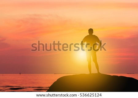 Silhouette of Man Standing enjoying on a Stone tropical sunset / sunrise Evening Sky at Beach Background, Happiness and active life Concept.