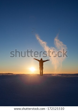silhouette of man standing in winter landscape and throwing snow  - stock photo