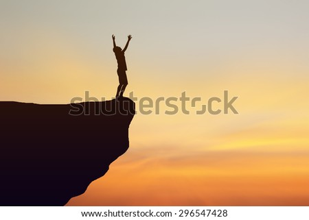 Silhouette of man standing on the cliff lift. Orange sky background - stock photo