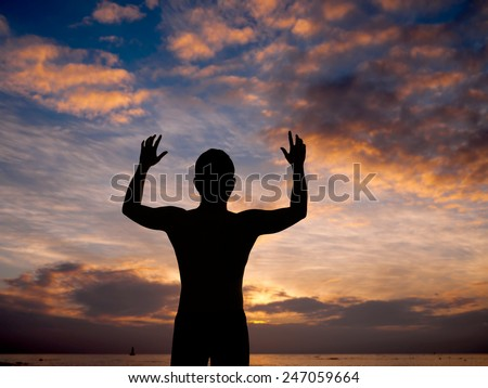 Silhouette of man surrendering with two hands raised in air near the beach at sunset