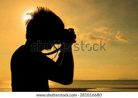 Silhouette of man take the photo at sunset on the beach of koh samui island - stock photo
