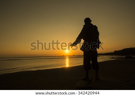silhouette of man trying to catch the sun during sunset at the beach - stock photo