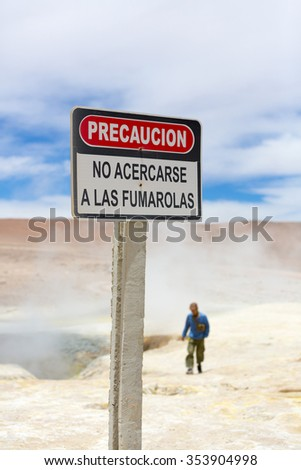 Silhouette of man walking behind a danger stop warning sign post in Solar de Manana geyser, Bolivia