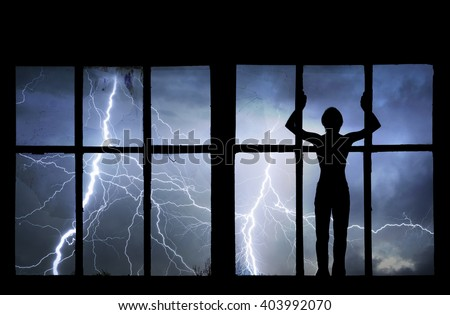 Silhouette of man watching lightning, thunder, rain and storm through broken window of old building.