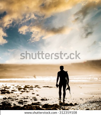 Silhouette of man with a surfboard on the beach at sunset - stock photo